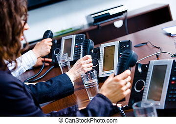 Customer Service - Close-up of hands holding landline phone...