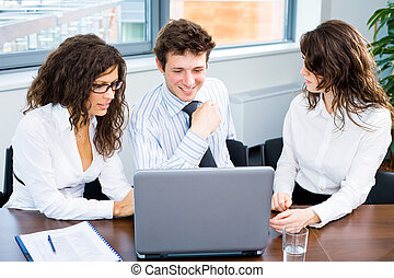 Business team with laptop - Happy young business people...