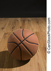 Basketball over wooden floor. Close up.