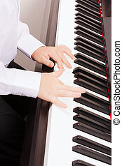 close up of child hands playing the piano - music and...
