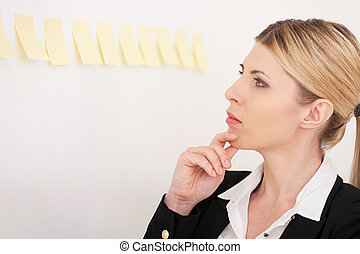 Planning her work. Side view of confident mature businesswoman pointing the adhesive notes attached to the wall