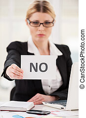 Rejection. Serious mature woman in formalwear saying no to...