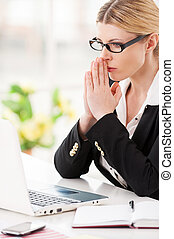 Businesswoman praying. Thoughtful mature woman in formalwear holding hands clasped and looking at the laptop while sitting at her working place