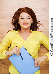 smiling female student with textbook and pencil - education...
