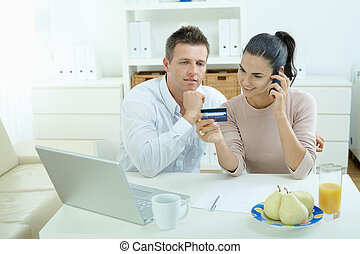 Couple shopping on internet - Young couple sitting at desk...