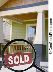 Sold sign - House for sale with sold sign and magnifying...