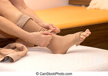 DVT stockings - Female putting thrombosis stockings on
