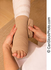 Pressure bandage - A pressure bandage is beeing applyed by a...