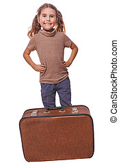 brunette girl smiling child standing next to suitcase for...