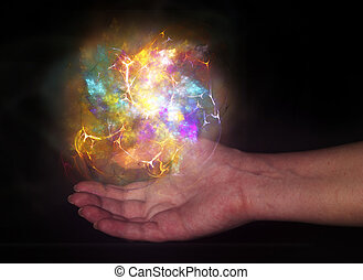 Bright light ball over human hand isolated on black...