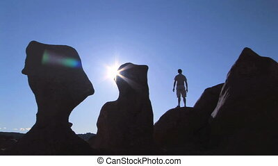 Man on rock in silhouette - Man climbing up onto a rock...