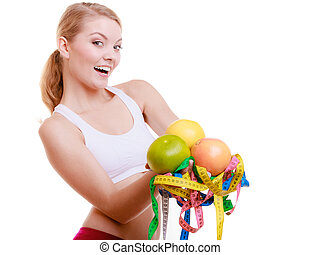 Sporty fit woman with measure tapes fruits. Time for diet slimming.