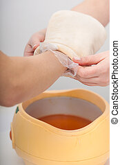 Female hand and orange paraffin wax bowl Woman in beauty...