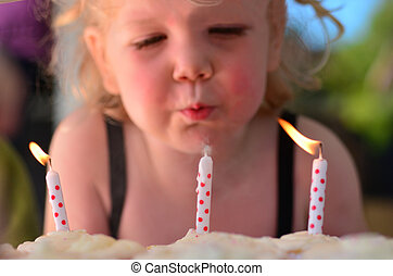 Little girl blows birthday candles during here third...