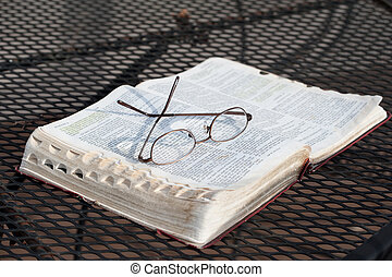 Bible on Iron Table - A closeup of a pair of reading glasses...