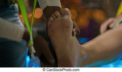 Man peeling female feet
