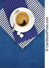 Cup of coffee - White cup of coffee on blue linen. Top view.