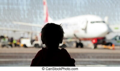 Little boy watching planes at the airport standing in...