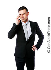 Handsome businessman talking on the phone over white...