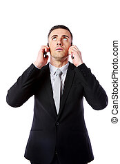 Businessman talking on two cell phones at the same time over...