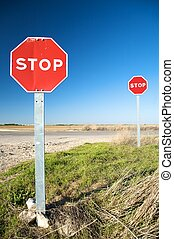 two stop signals - stop traffic sign next to road in...