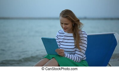 Woman with touchpad by the sea - Dolly shot of a young woman...