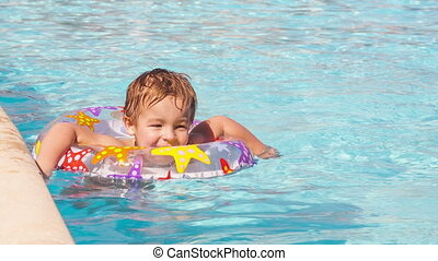 Boy swimming with inflatable ring - Cute little boy swimming...