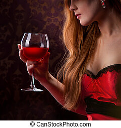 elegant woman holding glass of red wine