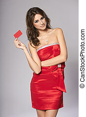 Fashion female in red dress showing red card - Beautiful...