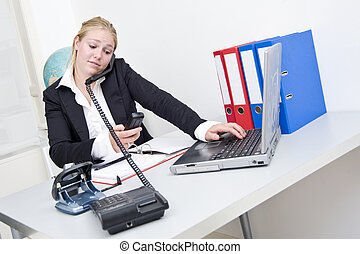 Multitasking - Young businesswoman doing several things...