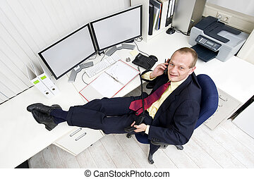 Entrepreneur - The owner of a small business relaxing behind...