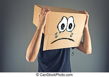 Man with cardboard box on his head and sad face expression -...