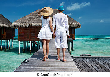 Couple on a beach jetty at Maldives - Couple on a tropical...
