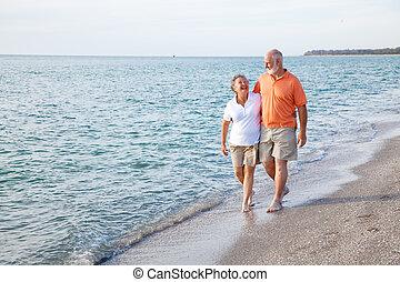 Seniors Walking on the Beach - Beautiful senior couple takes...