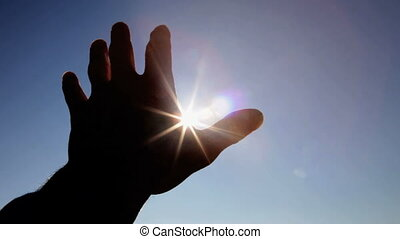 Hand in silhouette against sun - Hand in silhouette raised...