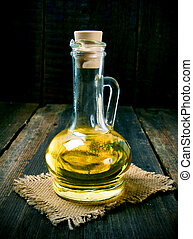 Olive oil in a vessel. On a wooden background.