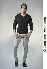 Full body photo of young man standing on grey background....