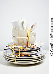 Dirty dishes pile needing washing up on white background -...