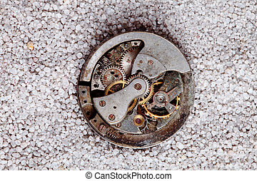 old clock - antique clock mechanism buried in sand