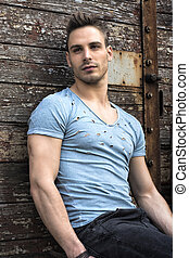 Young man sitting against old wood wall. Looking away