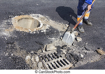Repairing sewer manhole - Utilities worker repairing sewer...