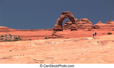 Delicate Arch - Nondescript tourists hiking in front of...