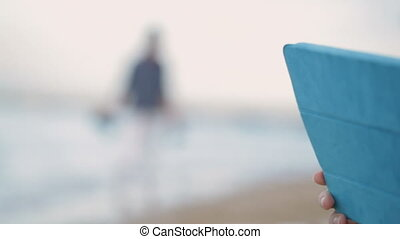 Boy and mother using pad on the beach