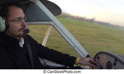 Pilot taking off on small airplane from grass field