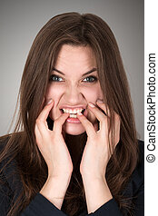 Frightened and stressed young business woman biting her...