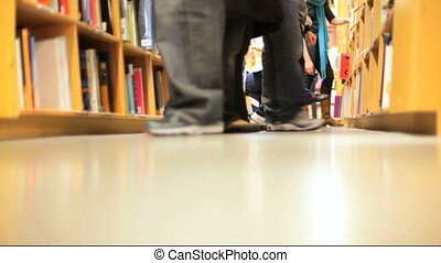 Book Shelves - People standing in front of stacks of books