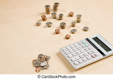 counting coins - stacks of change and calculator on desk