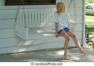 Girl on Swing - A young girl sits happily on a white porch...