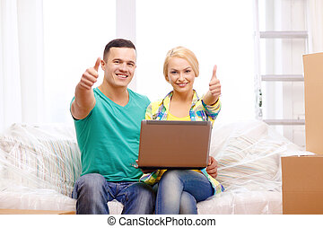 couple relaxing on sofa with laptop in new home - moving,...