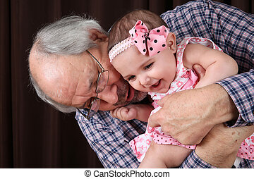 Grandfather and granddaughter - Grandfather cuddling his...